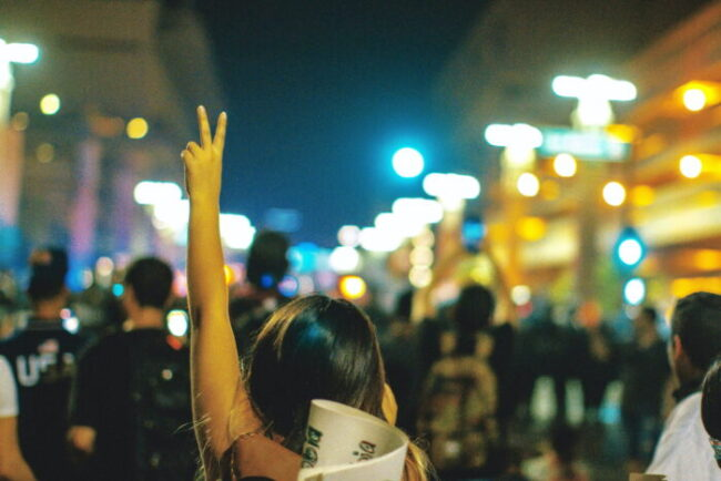 Working as a career professional in a difficult country, young woman holds up a peace sign during a public demonstration/protest