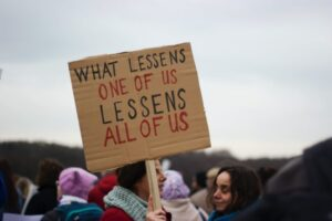 Protest sign: what lessens one of us lessens all of us
