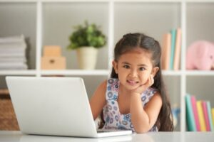 Smiling little girl at laptop